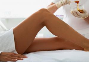 Kosmetikerin beim Auftragen von Wax zur Enthaarung